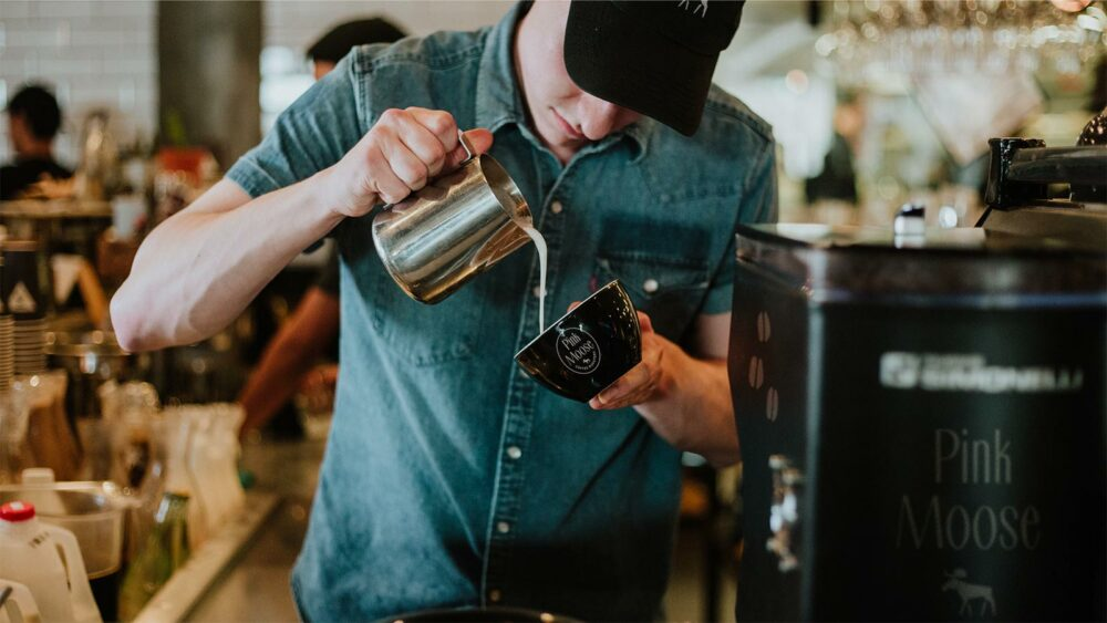 man pouring cream into a branded coffee mug